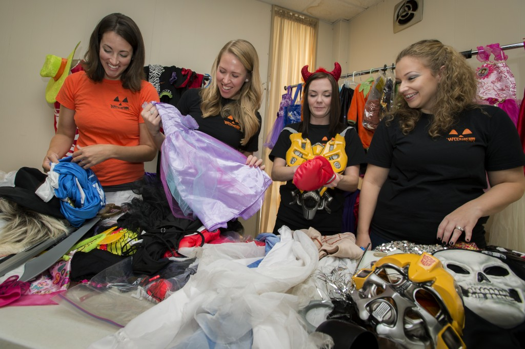'WEEN DREAM Board Members Valerie Gernhauser (L '09), Kelsey Meeks (L '10), Alli Scott Craig and Tara Benoit-Rodrigue (a 2014 Tulane Continuing Studies grad) sort donated garb so kids in need can dress up for Halloween. Photo by Paula Burch-Celentano.