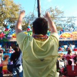 Joaquin de Obarrio (LLM '15) aims to catch beads along St. Charles Avenue. Photo by Dennis Zhao.